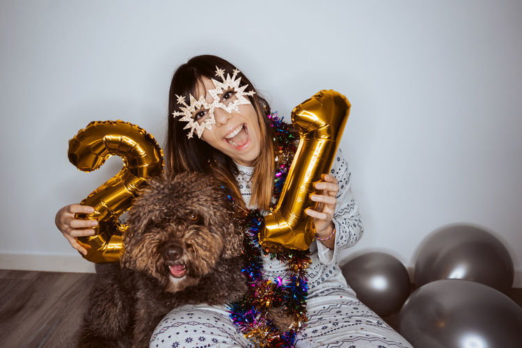Portrait of woman wearing mask sitting with dog and balloons on floor at home