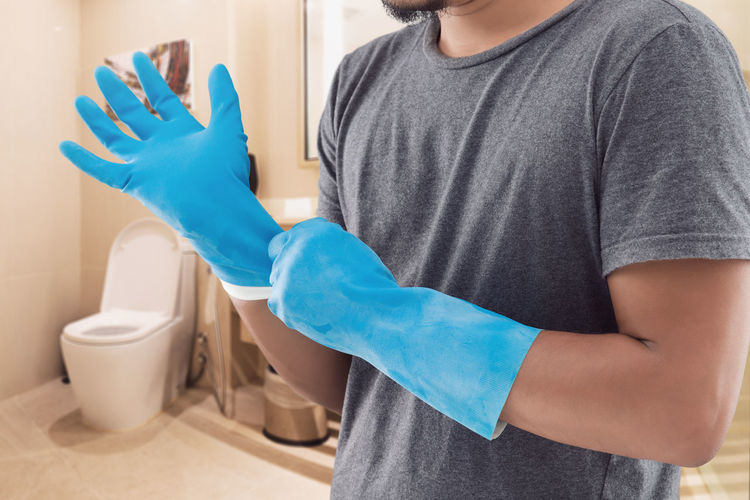 The man in a gray shirt wearing blue rubber gloves before washing the toilet.