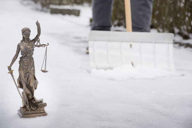 Low Section Of Person Shoveling Snow By Lady Justice Statue