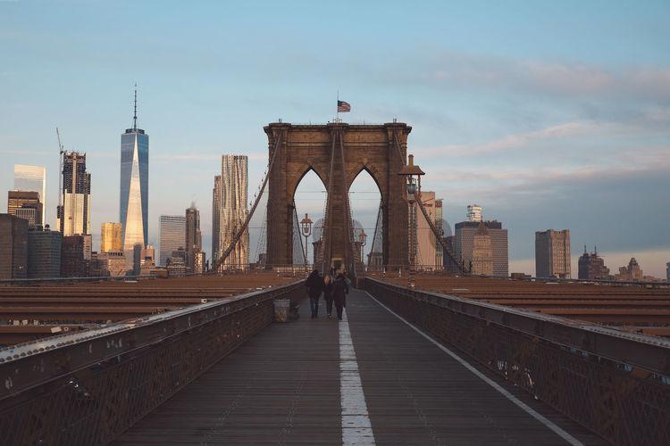 Rear view of people walking on brooklyn bridge in city