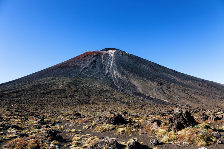 Low angle view of volcano against clear blue sky