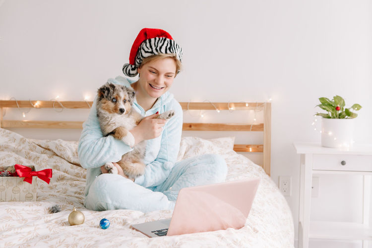 Portrait of smiling woman with dog sitting against wall