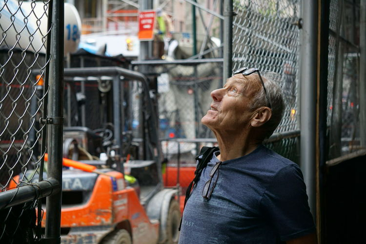 Thoughtful Senior Man Standing By Fence In City