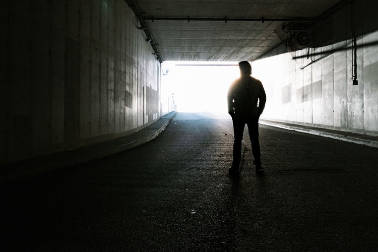 Rear view of silhouette man in tunnel