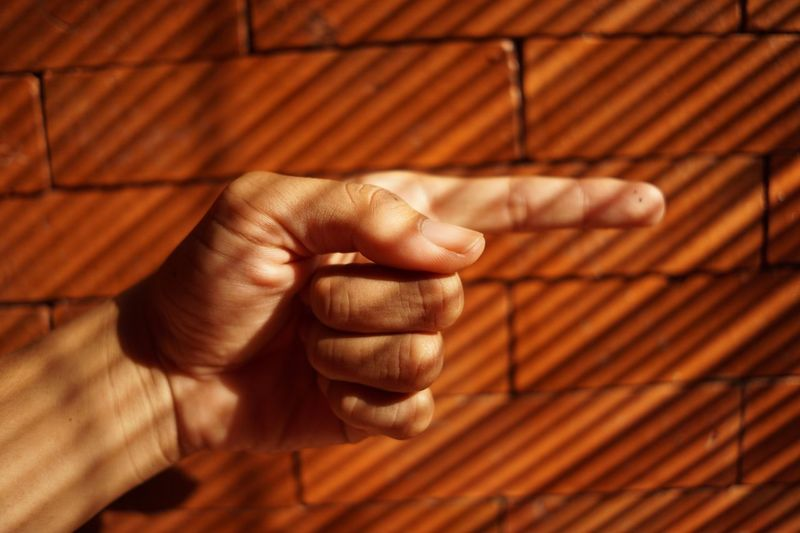 Cropped image of hand gesturing against brick wall