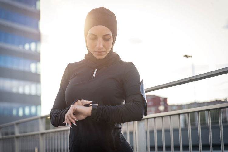 Beautiful woman wearing hijab standing against building during sunrise