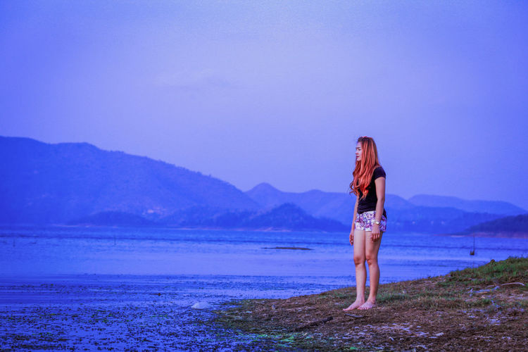 Girl Standing On The Lake. Adult Beach Beauty In Nature Full Length Girl Standing Hairstyle Land Leisure Activity Lifestyles Mountain Nature One Person Outdoors Real People Scenics - Nature Sky Standing The Lake Tranquility Water Women Young Women Inner Power