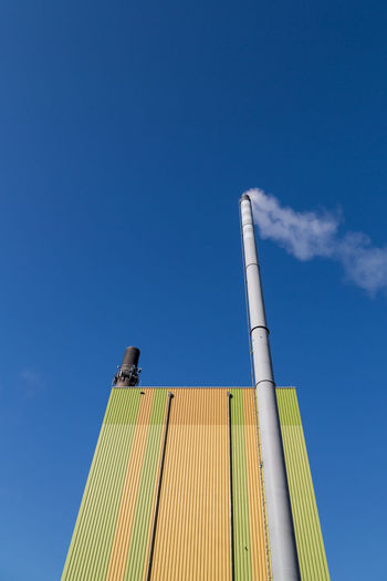 Low Angle View Sky Built Structure Architecture Building Exterior Factory Industry Copy Space Blue Day No People Clear Sky Smoke Stack Outdoors Tall - High Sunlight Environmental Issues Pollution Directly Below Pattern Metal Climate Change Lines And Shapes