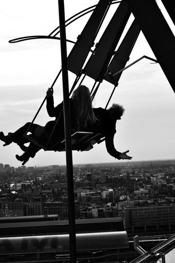 Hello World or... Goodbye? 😜 Outdoors Real People Silhouette People Photography Swing Swinging View From The Top Blackandwhite Cityscape Amsterdam City Adrenaline Eye4photography  EyeEm Gallery Malephotographerofthemonth Capture The Moment Togetherness Having Fun The Human Condition From My Point Of View From Where I Stand EyeEm Best Shots Hanging Hand B&w City Cityscape Sky Rope Swing