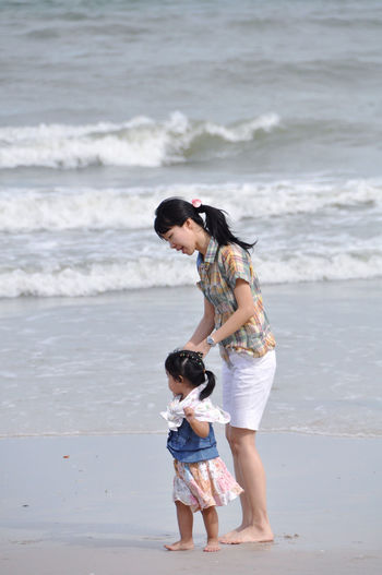Rear view of mother and daughter standing on beach