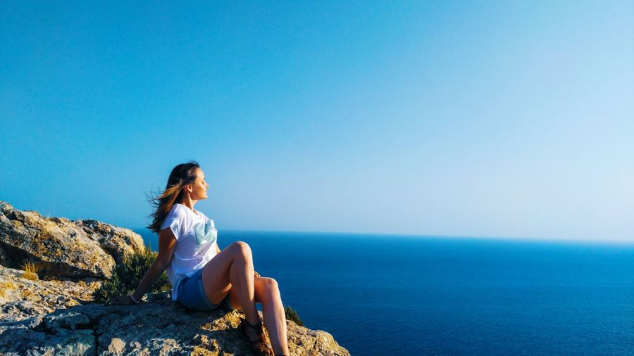 Woman sitting on rock by sea against clear blue sky