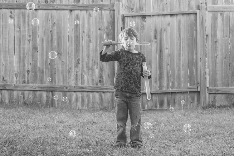 Full length of boy blowing bubbles while standing against fence