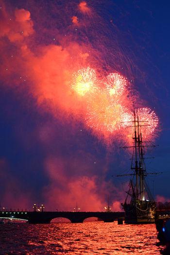 Sailboat sailing in river against fireworks at dusk
