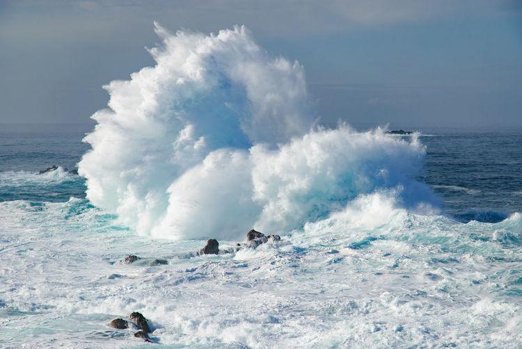 Huge waves crashing on sea against sky