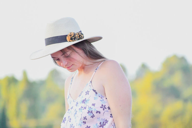 Pregnant woman wearing hat against sky