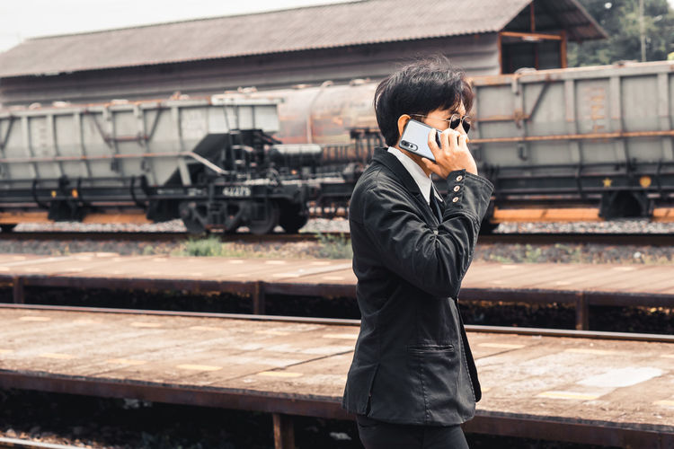 Full length of man using mobile phone while standing on railroad tracks