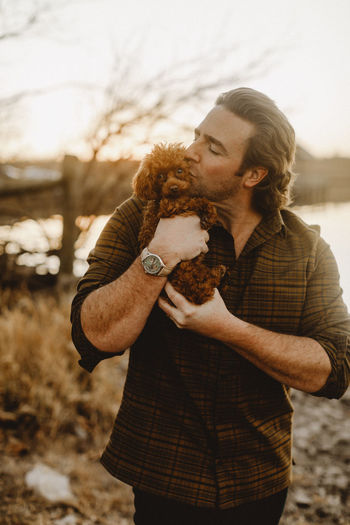 Midsection of man holding puppy standing outdoors