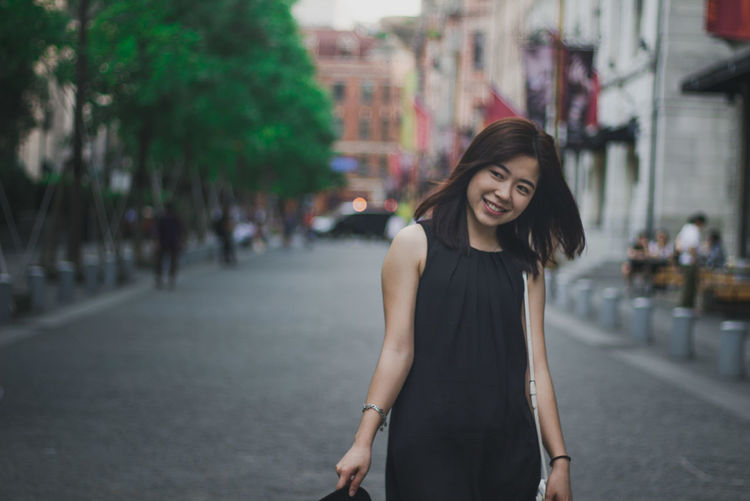 Smiling young woman standing against buildings in city