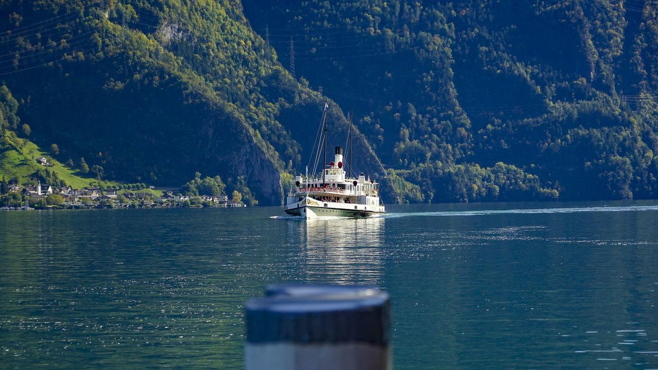 SHIP SAILING ON SEA AGAINST MOUNTAINS
