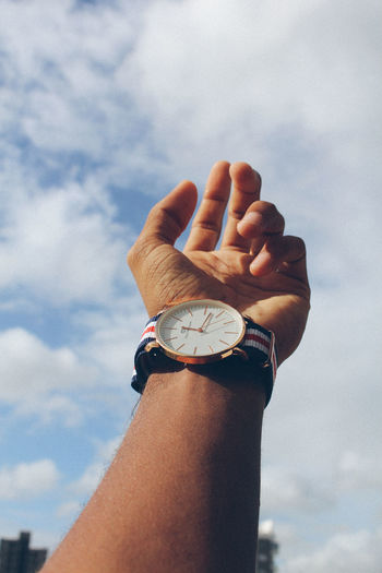 Cropped Hand Of Man Wearing Wristwatch Against Sky