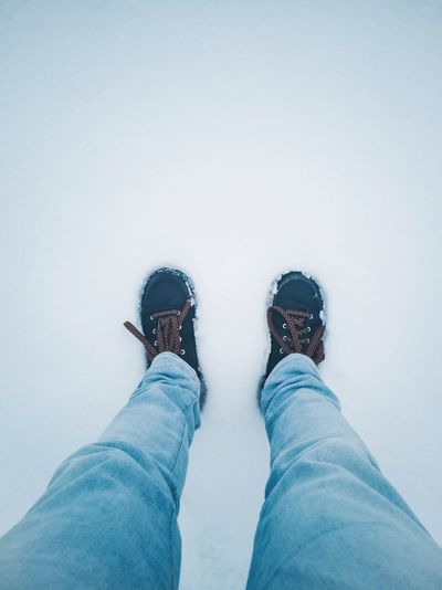 Low section of man standing on snowy land