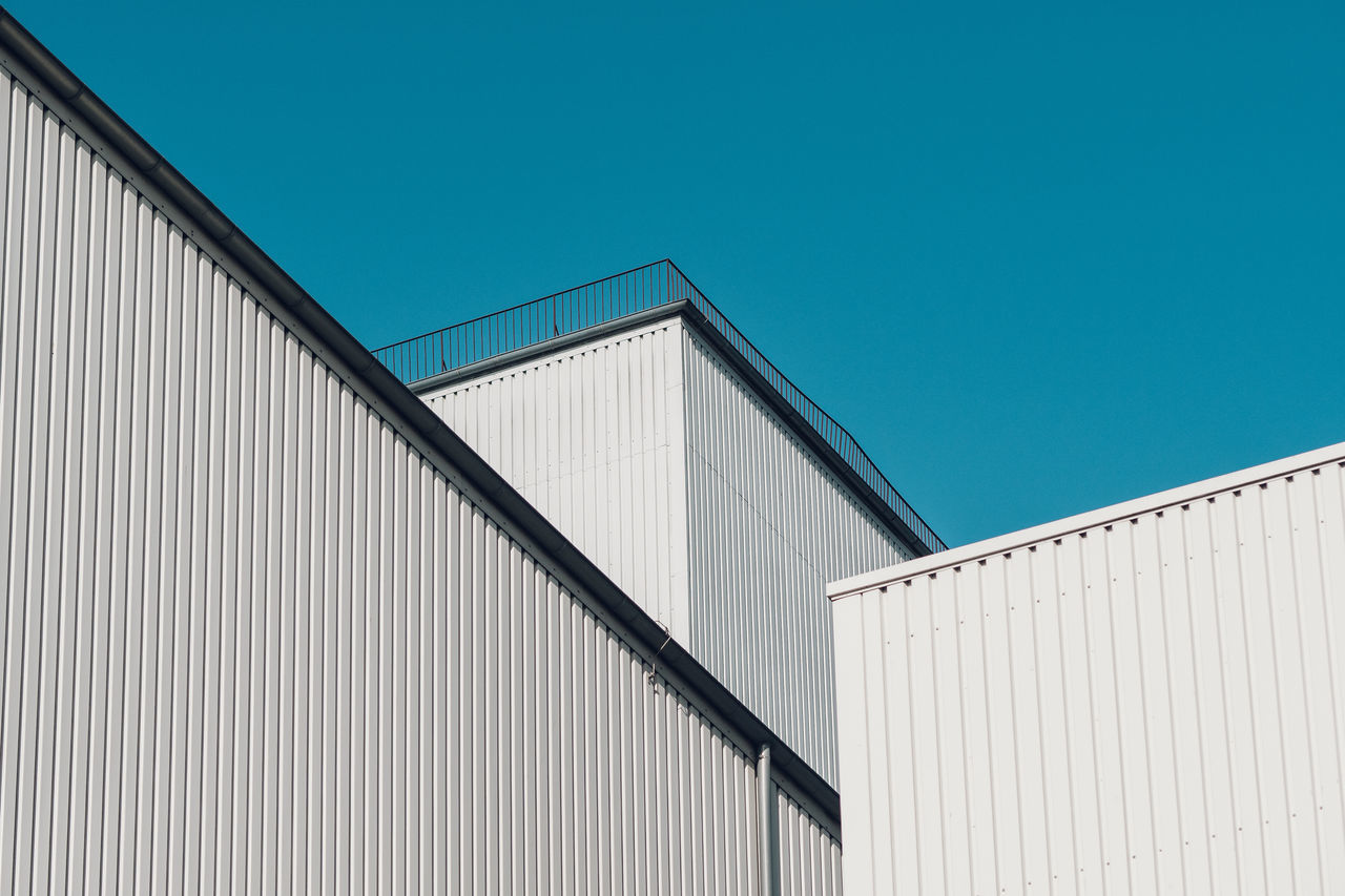 Low angle view of industrial building against clear blue sky