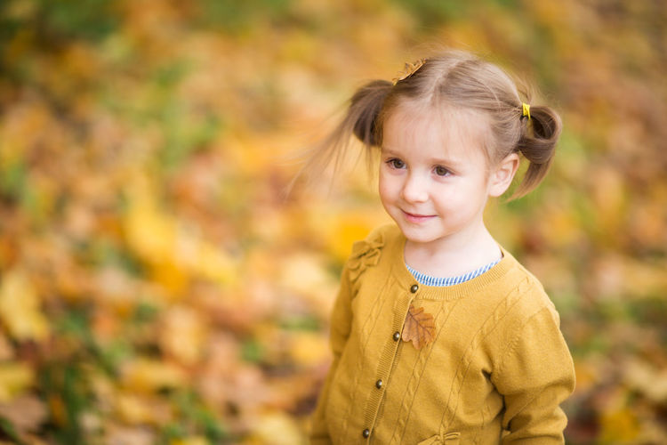 Portrait of a smiling girl with autumn leaves