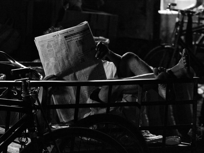 Man reading newspaper on bench at night