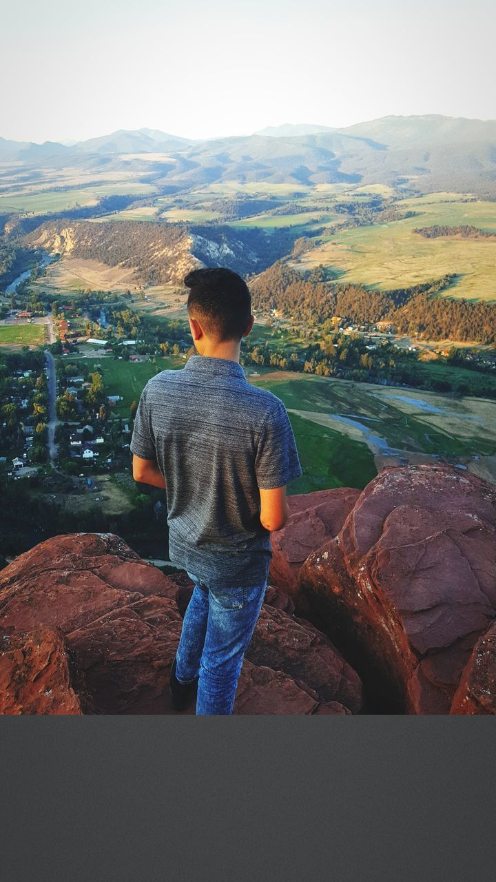 real people, rear view, mountain, one person, rock - object, day, nature, standing, landscape, full length, leisure activity, lifestyles, outdoors, beauty in nature, scenics, men, sky, young adult