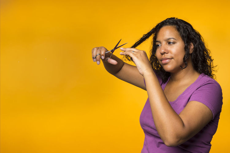 Woman Cutting Her Hair Over Orange Background