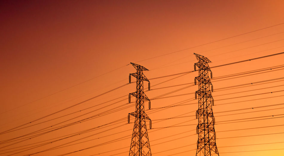 Low angle view of electricity pylon against orange sky. high voltage electric pole.