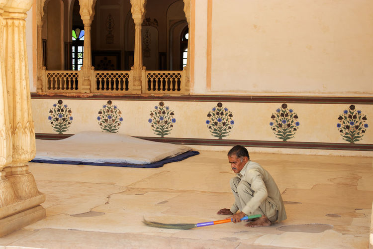Man brushes floor at Jairgarh Fort, Jaipur One Person Architecture Sitting Real People Built Structure Window Occupation Building Jairgarh Fort India Jaipur Rajasthan Fort Broom Cleaning