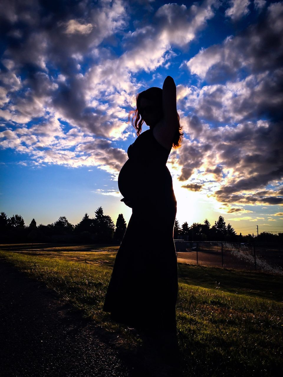 Side View Of Silhouette Pregnant Woman Standing On Field At Sunset