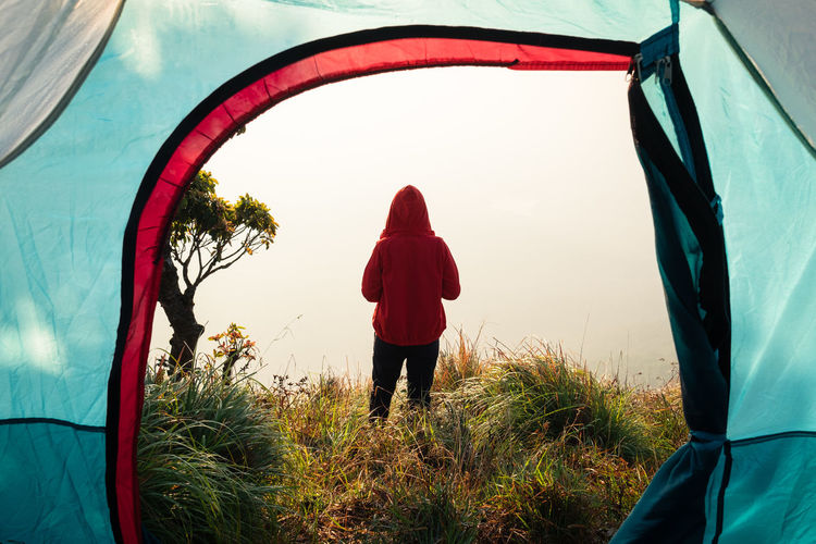 Rear View Of Man Standing On Field Seen Through Tent