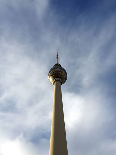 Low angle view of communications tower against cloudy sky