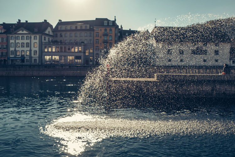 Water Splashing From Fountain In Pond By Buildings Against Sky