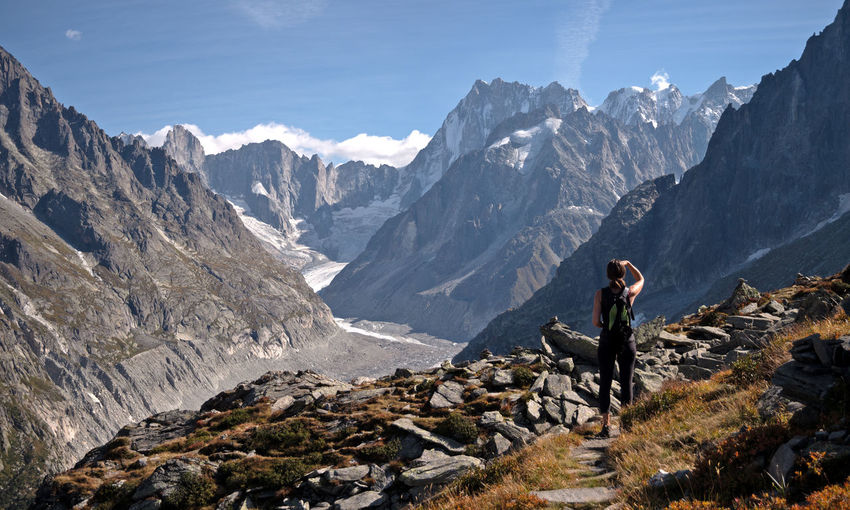 A lone female Hiker looks out over a glacier valley in the region of Chamonix in the alps of France. High alpine snow covered mountains surround the foreground rocks and alpine terrain. Adventure Beauty In Nature Day Formation Full Length Hiking Leisure Activity Lifestyles Mountain Mountain Range Nature Non-urban Scene One Person Outdoors Real People Rock Rock - Object Scenics - Nature Sky Solid Standing