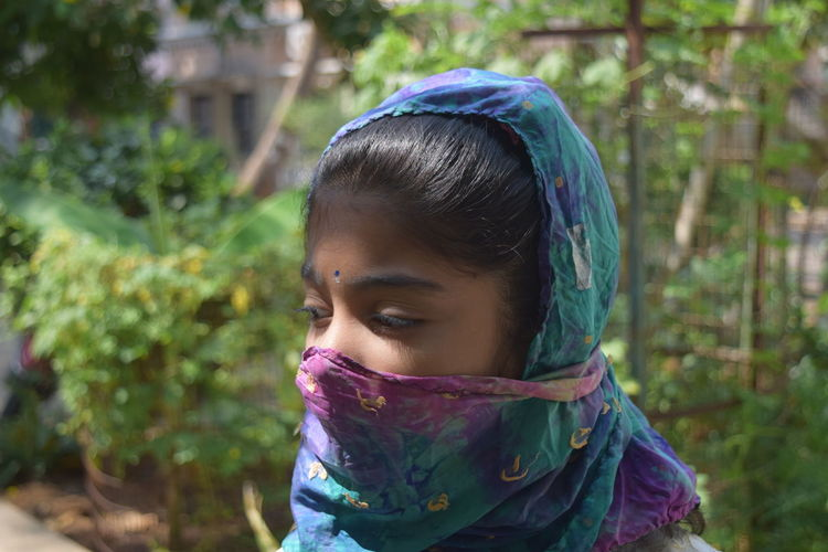 Close-up of girl covering face with scarf