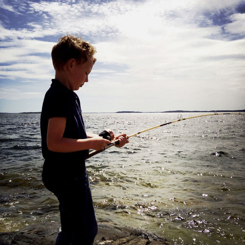 A young boy fishing on the rocks by the water. Beach Beauty In Nature Boy Cloud - Sky Fishing Leisure Activity Lifestyles Nature One Person Outdoors Sea Sky Water