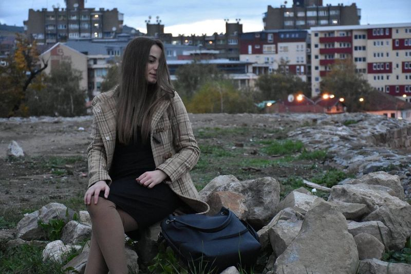 Woman sitting on rock at field in city