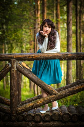 Young Woman Leaning On Wooden Railing Of Footbridge At Forest