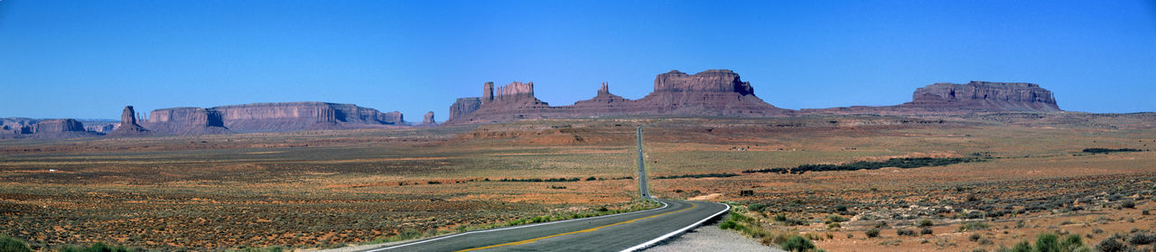 Road passing through landscape against clear blue sky