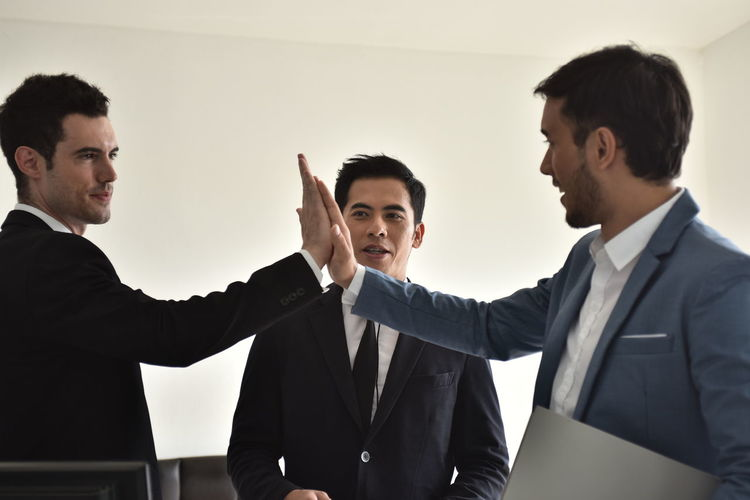 Businessman Young Men Young Adult Indoors  Men Business Person Males  Business Coworker Waist Up Office Well-dressed Cooperation Adult Corporate Business Standing Colleague Group Of People Teamwork Meeting Human Arm
