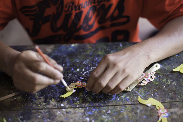 Cropped image of person making crafts