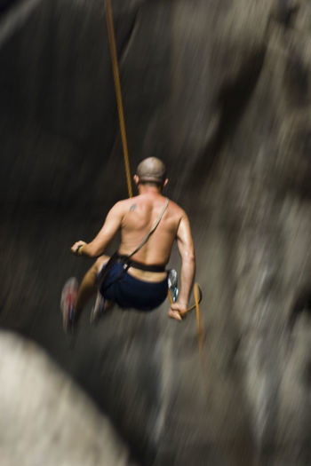 Low angle view of shirtless man rappelling on rock formation