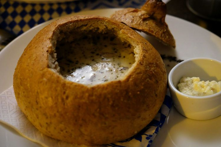 Close-up of sour rye soup in bread bowl on table