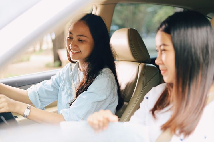 Mode Of Transportation Transportation Women Vehicle Interior Two People Real People Car Young Women Travel Motor Vehicle Lifestyles Adult Leisure Activity Smiling Happiness Young Adult Sitting Togetherness Car Interior Hairstyle Outdoors Positive Emotion