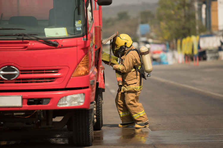 Firefighter standing by fire engine on street