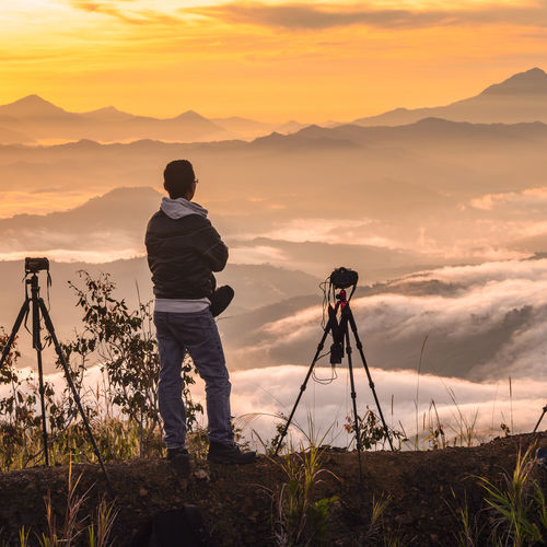 Man standing on mountain ledge high above clouds during sunrise. Sabah MY Adult Adults Only Adventure Camera - Photographic Equipment Cloud - Sky Cloudscape Full Length Hiking Lake Mid Adult Mountain Nature Nature Reserve One Man Only One Person Only Men Outdoors People Photographer Photographing Photography Themes Scenics Sky Sunset Tripod