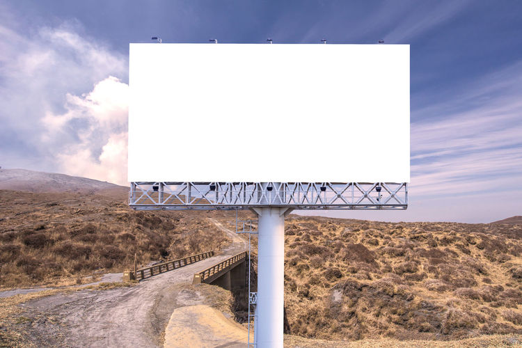Advertisement Arid Climate Billboard Blank Climate Cloud - Sky Communication Copy Space Day Environment Land Landscape Mountain Nature No People Outdoors Road Road Sign Sign Sky Sunlight Text